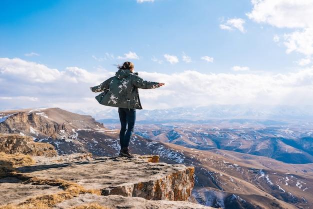 アクティブな若い女の子が旅行し、山の端に立って、自然を楽しんでいます