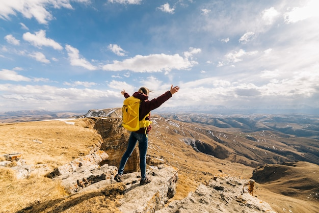 Active young girl travels through the caucasian mountains, with a yellow backpack, enjoys the sun
