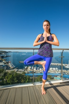 Active young girl in a tree pose on an open terrace on the background of the sea.