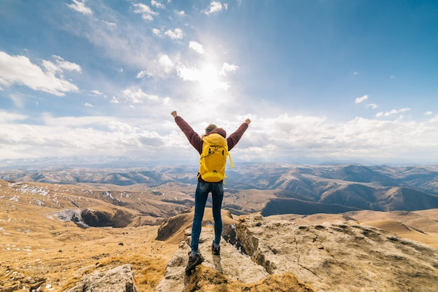 Active young girl with a yellow backpack travels along the caucasian ridge, enjoys the sun