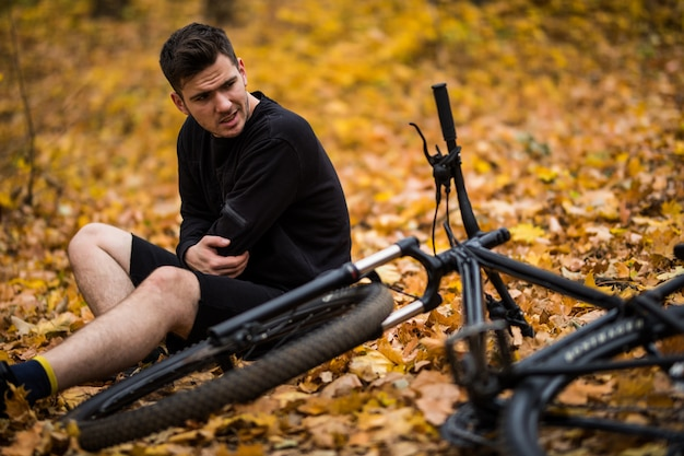 Active young man holding by his hurt or broken hands while lying on autumn forest path by his bicycle