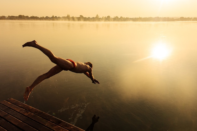 Активный молодой человек в красных плавках прыгает в воду с деревянного пирса.