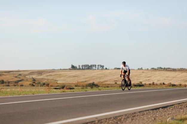 화창한 날 동안 도로에 운동 몸 자전거와 활성 젊은 남자