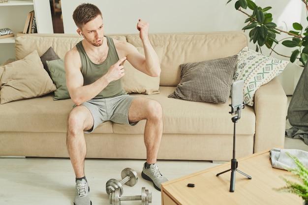 Активный молодой мускулистый мужчина, указывая на свой бицепс, объясняя перед камерой смартфона, что он делает, чтобы оставаться в хорошей форме
