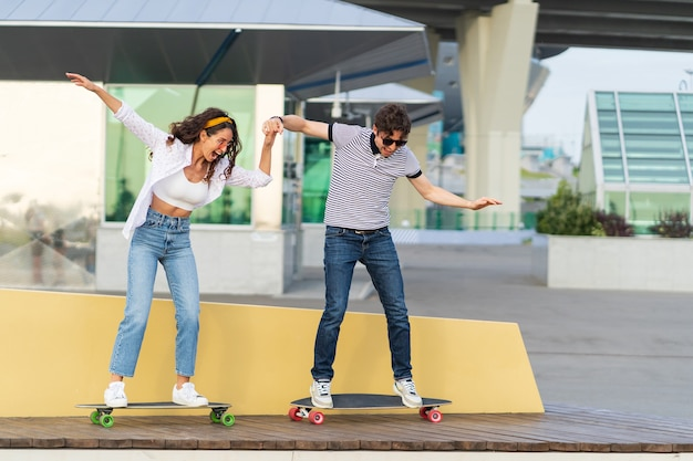 Active young skaters couple learn to ride longboard together hold hands laughing stand on skateboard