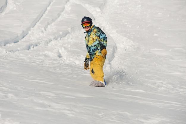 明るい冬の日に雪の丘を下って乗って明るいスポーツウェアでアクティブな若いスノーボーダー
