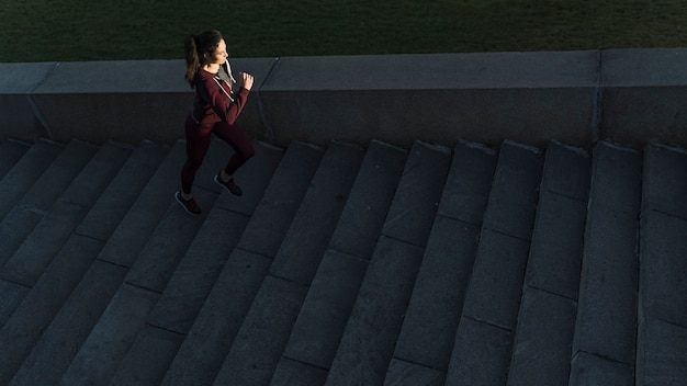Active young woman climbing stairs