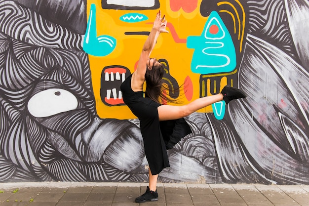 Active young woman dancing against graffiti wall