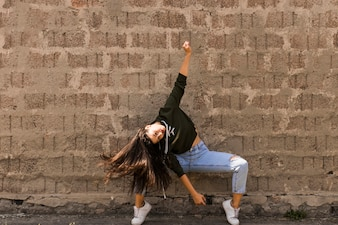 Active young woman dancing against old wall