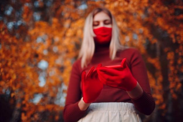 携帯電話で秋の公園で赤い手袋とフェイスマスクのアクティブな若い女性