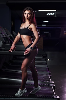 Active young woman and man running on treadmill in gym.