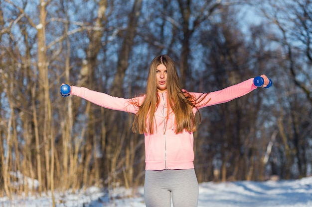 Active young woman performs an exercise with a dumbbells