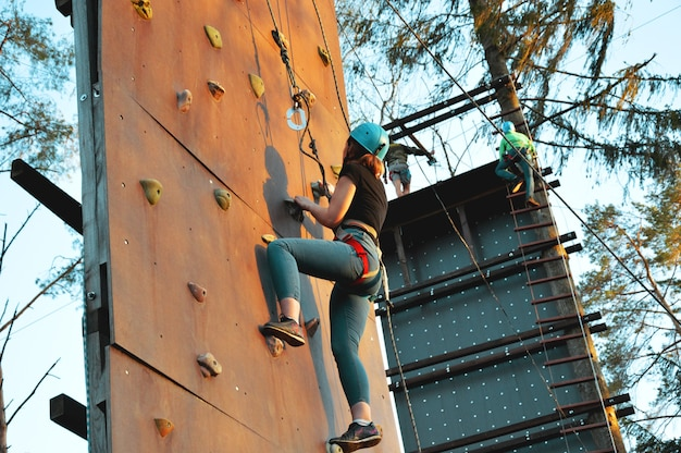 Active young woman on rock wall in sport center - outdoors