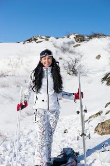 Активная молодая женщина в лыжном снаряжении, стоя на снегу и улыбаясь в камеру.