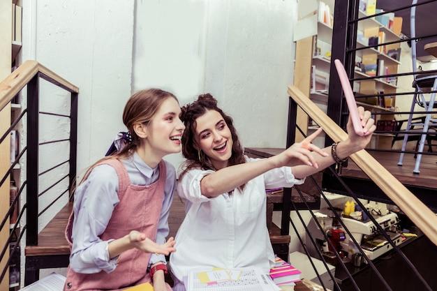 Активно жестикулирует. активная молодая темноволосая дама поднимает руку с планшетом и фотографируется с другом