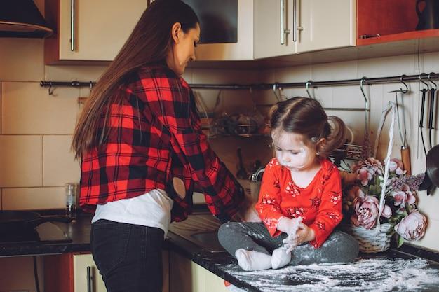 コロナウイルス検疫における子供のための活動。両親が子供を忙しいママと幼児の娘が台所で遊ぶ方法