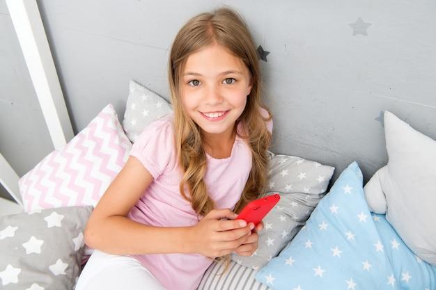 Мероприятия для пижамной вечеринки. девушка ребенок носить пижаму держать смартфон. ребенок в пижаме держит смартфон. идеи для пижамной вечеринки. девушка ищет в интернете идеи для своей домашней вечеринки. вечеринка с ночевкой.