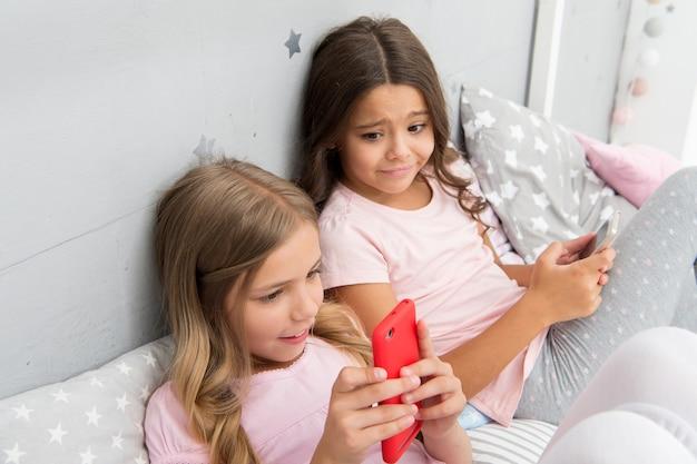 パジャマパーティーの活動。女の子、子供、親友、姉妹はスマートフォンで忙しいパジャマを着ています。パジャマ姿の子供たちはスマートフォンと対話します。子供世代のためのテクノロジー。パジャマパーティーのアイデア。