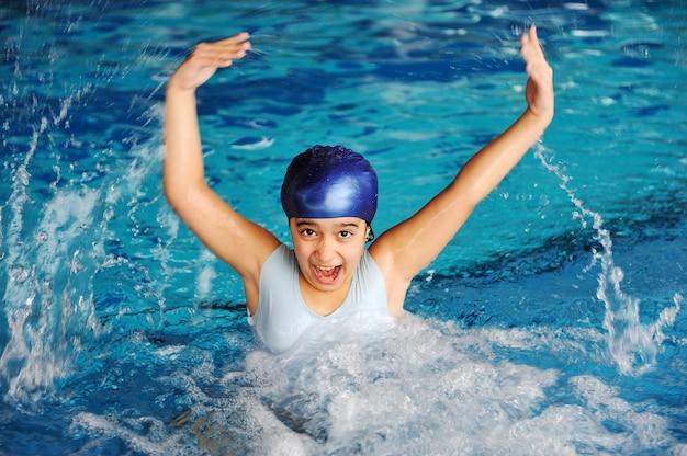 Занятия в бассейне, плавание и игра детей, брызги девушки