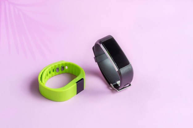 Activity smart trackers with shadow of palm leaf, sport bracelets