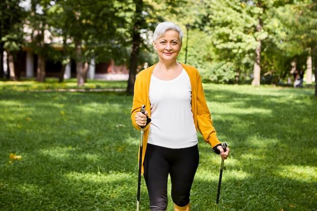 활동, 웰빙, 스포츠 및 은퇴 개념. 공원에서 스칸디나비아 산책을 즐기고 특별한 막대기로 야외에서 포즈를 취하는 세련된 사이클링 반바지와 카디건에 매력적인 맞는 노인 여성
