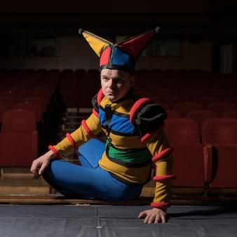 Актер одел костюм шута в интерьер старого театра.