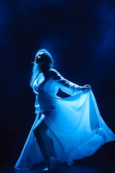 Actress / singer on stage in the rays of blue light.