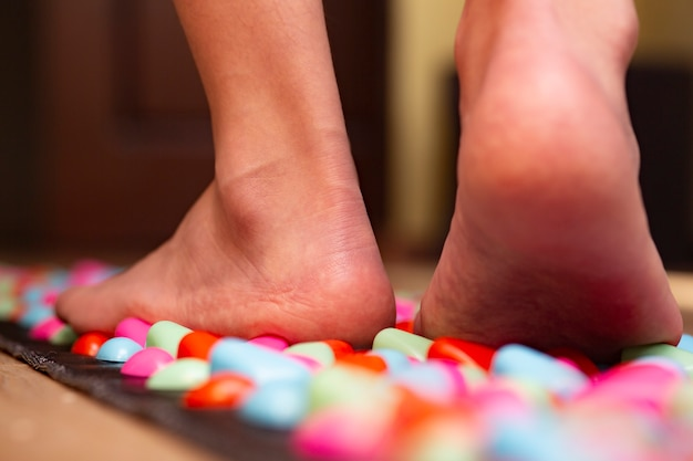 Acupuncture points of the foot stimulation massage mat for home walkway in the form of plastic stones treatment of diseases by pressing points on the foot selective focus