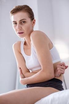 Острая боль. больная молодая женщина держится за живот, чувствуя сильную боль