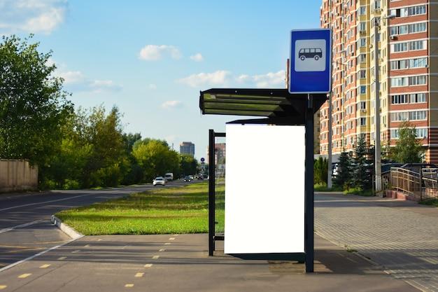 バス停の広告街の通りのバス停にある垂直の白い看板夏の晴れをからかう