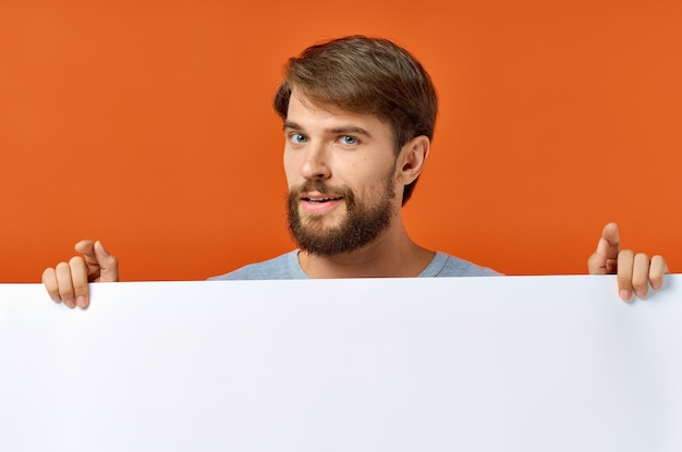 Ad poster in the hands of a man on an orange background gesturing with his hands copy space mockup.