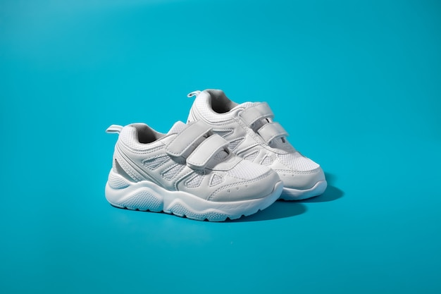 An ad for white teen sneakers standing sideways on an isolated blue paper background with harsh sunl...