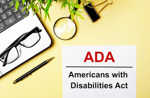 Ada americans with disabilities act is written in red on a white piece of paper on a light yellow background next to a laptop, pen, magnifying glass, glasses and a green plant