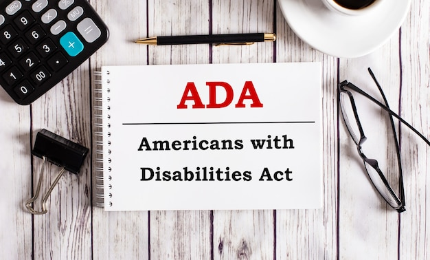 Ada americans with disabilities act is written in a white notepad near a calculator, coffee, glasses and a pen