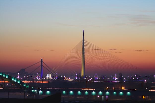 セルビア、ベオグラードの日没でサヴァ川のエイダ橋