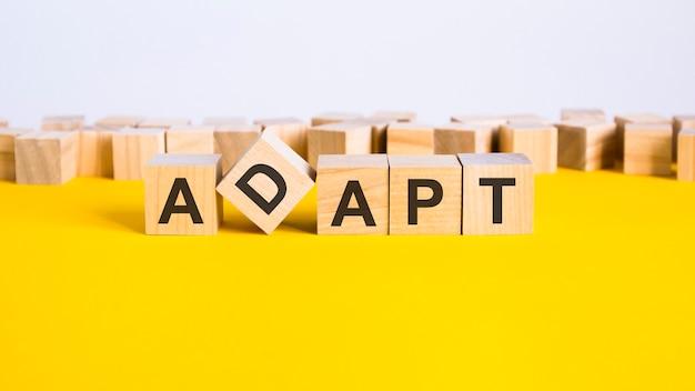 Слово adapt состоит из деревянных строительных блоков, лежащих на желтом столе, концепция