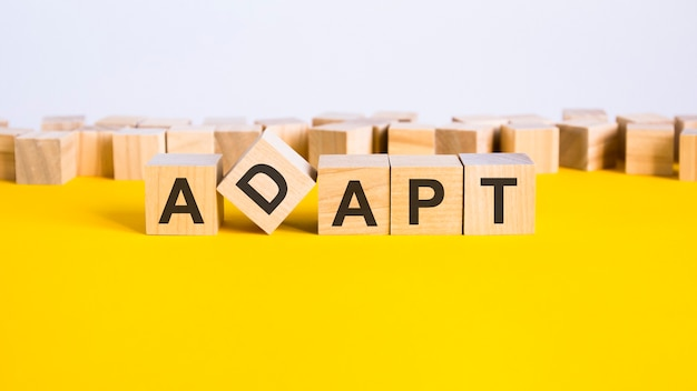 Adapt word is made of wooden building blocks lying on the yellow table, concept