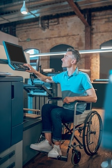 Adaptation. joyful young adult man on wheelchair managing copier workflow using computer in office space