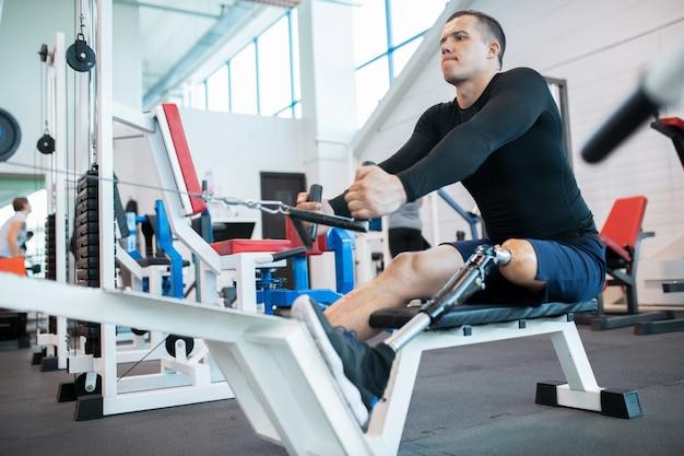 Адаптивный спортсмен с использованием тренажера