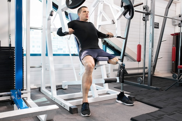 Адаптивный спортсмен работает в тренажерном зале