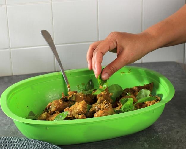 Добавить лист базилика (даун кеманги) в маринованную курицу, приготовить пепес аям, индонезийскую курицу на пару с бананом в обертке