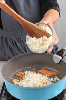 Добавить рис в сковороду, приготовить наси горенг (жареный рис)