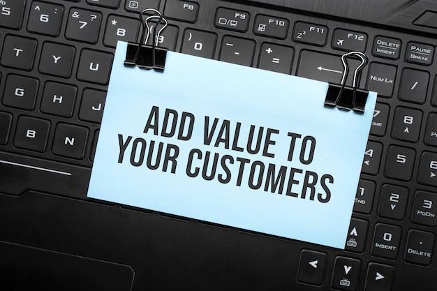 Добавить стоимость для ваших клиентов надпись на белой бумаге на клавиатуре ноутбука