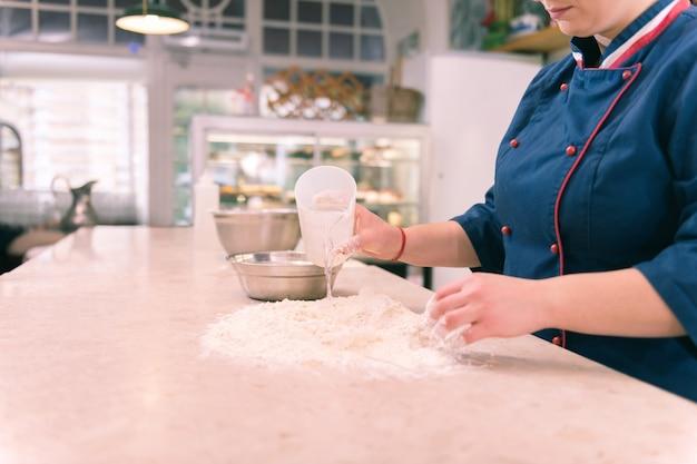 水を加える。青いジャケットを着たパン屋は、一生懸命働いている間、クロワッサンの生地に水を加えます