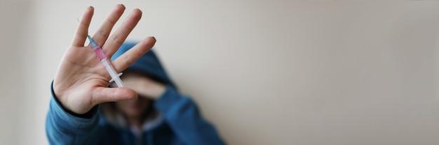 Наркоман держит в руке шприц с иглой