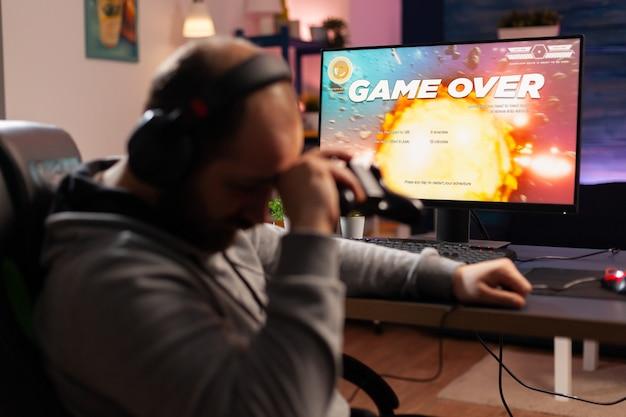 ヘッドフォンとワイヤレスジョイスティックを使用してスペースシュータービデオゲームを失う中毒ゲーマー。動揺したプレーヤー。ゲームルームで深夜にオンライントーナメントにプロの機器を使用して敗北したゲーマー
