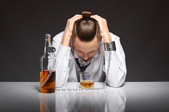 Addicted man looking at his glass of whiskey