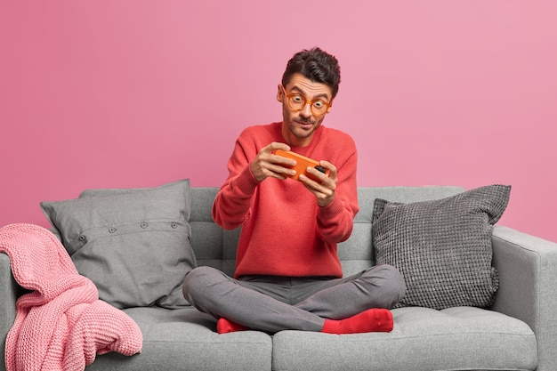 Addicted man plays online games on smartphone sits crossed legs at comfortable sofa