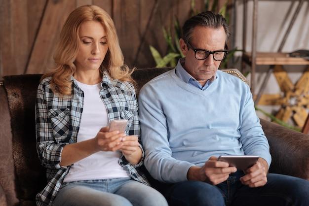 Зависимая зрелая сосредоточенная пара сидит на диване и пользуется мобильными телефонами во время серфинга в интернете и выражает апатию