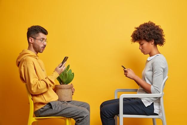 Una coppia multirazziale dipendente usa i propri telefoni cellulari per la comunicazione online, si siede l'uno di fronte all'altro sulle sedie, ha la dipendenza da internet, trascorre il tempo libero a casa